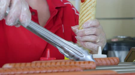 kiełbasa : Employee prepares top loader hotdog in fast food takeaway restaurant