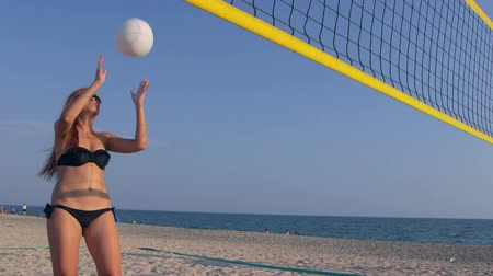teen action : Young girl spends summer vacation on the beach playing volleyball with friends