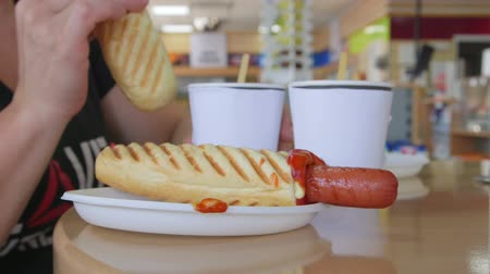 conveniência : People eating hot dogs with coffee at table in convenience store