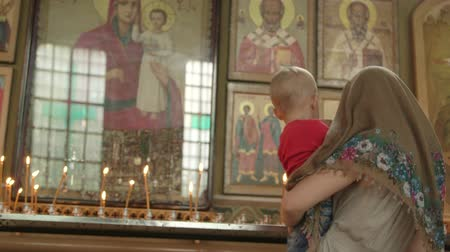 modlitba : Mother with child lighting prayer candle in Christian Orthodox Church