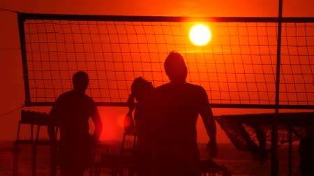 fit : Recreational game of beach volleyball on public beach in the evening Stock Footage