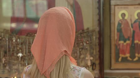 iconography : Young woman worshipper praying in Christian Orthodox Church rear view close-up  Stock Footage