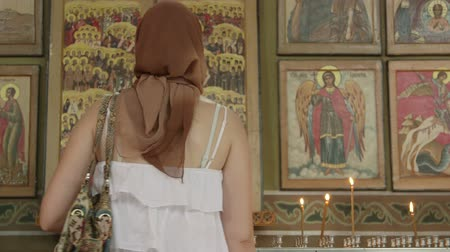 iconography : Christian women prayer before icons in Russian Orthodox Church