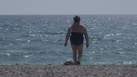 senior lifestyle : Overweight senior woman walking on the beach rear view Stock Footage