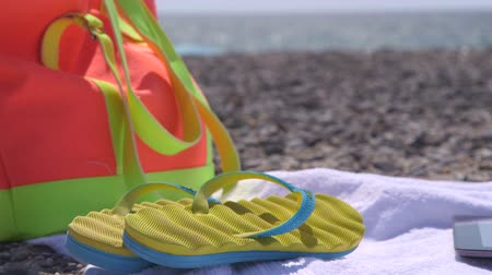 towel : Colorful bag flipflops and towel at summer beach Stock Footage