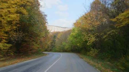 fall down : Driving car on mountain road through fall foliage Stock Footage