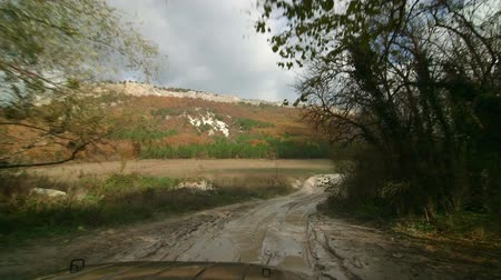 jumble : Four-wheel drive vehicle driving through a muddy puddle on dirt road in direction of Mangup,  Crimean mountains Stock Footage