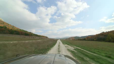 jumble : SUV driving on dirt road through the valley near Crimean Mountains,  Mangup, Crimea Stock Footage