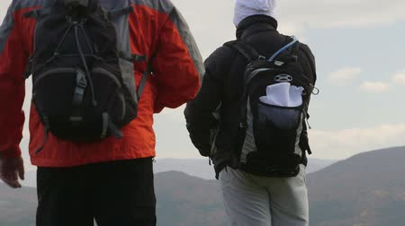 two people : Hiking people standing with backpacks on cliff edge and looking at mountain landscape