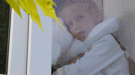 yedek : Little girl looking out window on rainy day in autumn