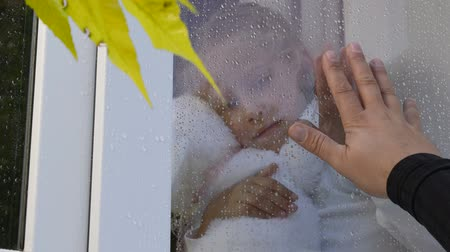 идущий : Father draws heart on glass looking at daughter through a window pane with raindrops in autumn Стоковые видеозаписи