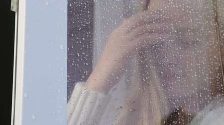 tizenéves lányok : Sad teenage girl looking out window with rain drops close-up view from outside Stock mozgókép