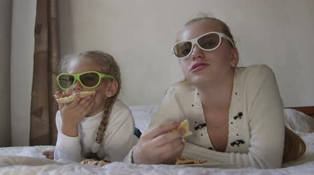 Little girl with sister eating pizza and  watching 3d TV Stock Footage
