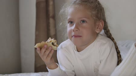 jeść : Little girl eating pizza and watching TV on the bed at home