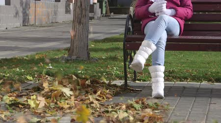 ботинок : Girl in white boots sitting on the bench wind blows fall foliage Стоковые видеозаписи