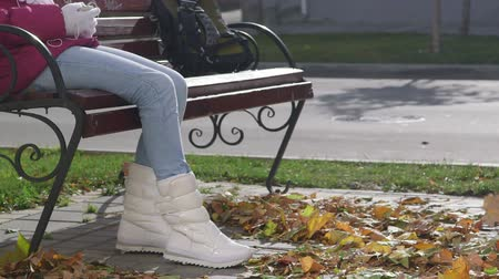 csizma : Girl in white boots sitting on the bench wind blows fall foliage Stock mozgókép
