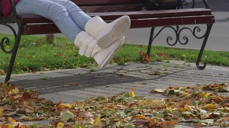 ботинок : Girl in new high top sneakers boots  sitting on bench in autumn close-up Стоковые видеозаписи