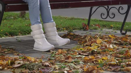bota : Female feet in white boots sneakers on pavement in fall foliage