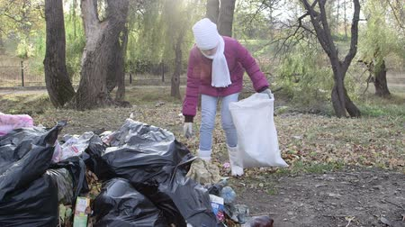 ajudar : Volunteer help clean up trash in park after holiday weekend