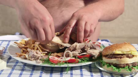 nadváha : Hungry overweight man eating fried chicken with french fries at home Dostupné videozáznamy