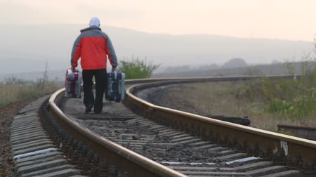 опасность : Passenger man with suitcases walking away on railway track