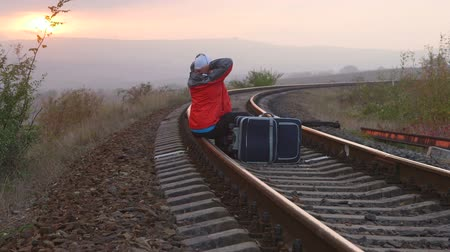 bagagem : Tired passenger with suitcases sitting on railroad track at sunset