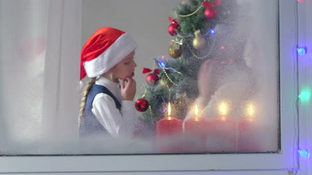 to celebrate : Funny kids celebrate Christmas around a decorated tree view through the window