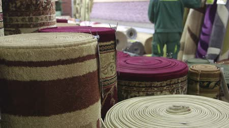halı : Rolls of rugs and carpets in flooring store staff serving customers