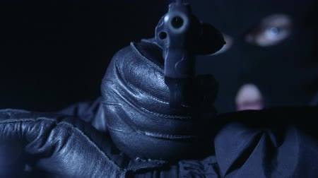 villain : Gloved hands with gun and flashlight aiming Stock Footage