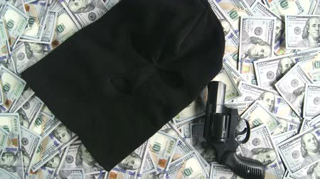 терроризм : Dolly: Balaclava and gun on pile of $100 american dollar banknotes as symbol criminal or terrorist activity