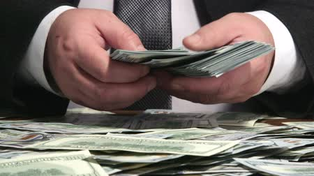 bank : Business person counting bundle of US 100 dollars bank notes at desk