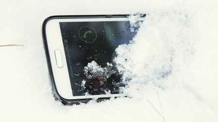клетка : Lost cell phone ringing in the snow closeup