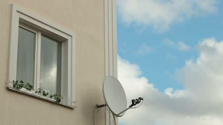 satelite : Window on wall of a house with satellite dish against sky with clouds