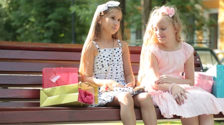 капелька : Fashion little girls in summer dresses having fun on a bench Стоковые видеозаписи