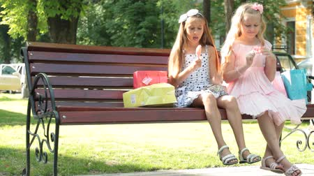 outside : Little girls with lollipops having fun on a bench in summer