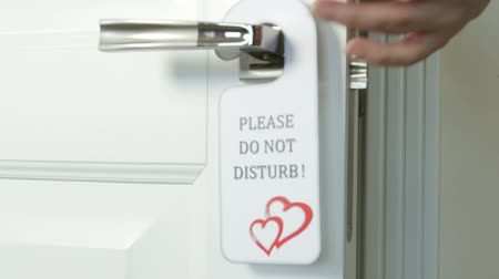 Door hanger Do Not Disturb with hearts on handle of hotel room Stock Footage
