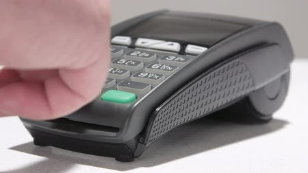 karta kredytowa : Hand swiping debit card through credit card terminal and entering PIN code Wideo