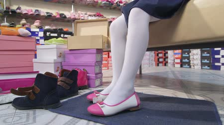 calçados : Little girl trying on new white pink ballet flats in children shoe store Stock Footage