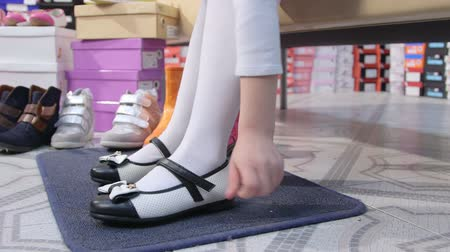 calçados : Little school girl trying on new black white flat shoes in children shoe store