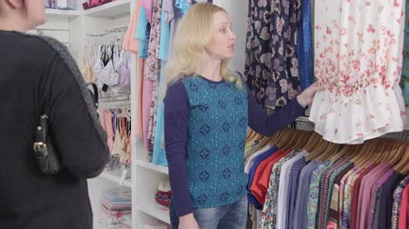 pomocník : Shopping for pregnancy clothes in baby and maternity store shop assistant helps a woman choose a dress