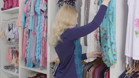 butik : Clothes shopping in clothing store woman looking for summer dress Stok Video