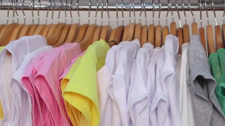 tshirt : Row of colorful shirts on hangers in a clothing store closeup Stock Footage