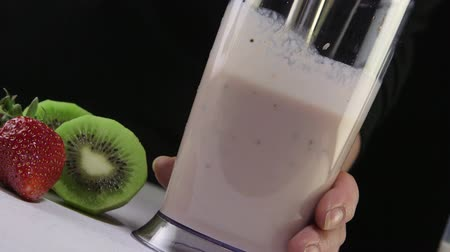 mikser : Dolly: Making kiwi strawberry smoothie drink using stick hand blender on a black background