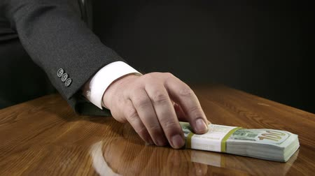 finanças : Hand of business man puts a wad of money on an office desk