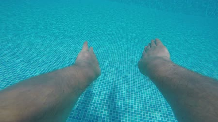 uszoda : SLOW MOTION: Swimmer jumping into blue water of outdoor hotel pool and swimming underwater PoV Stock mozgókép