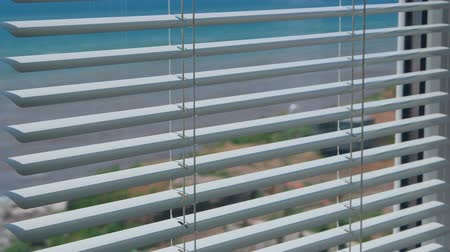 persiana : Sea view through the open window blinds close-up Stock Footage