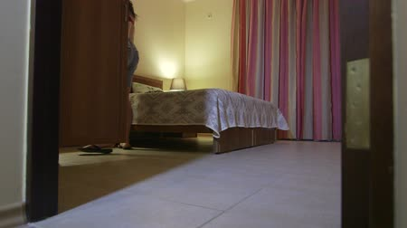alma : Woman taking off her top in bedroom of the hotel room