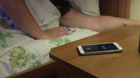 clock hands : Woman sleeping on bed with alarm clock on digital cell phone display Stock Footage