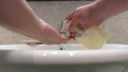 banyo : Man washing hands with liquid soap in the bathroom PoV Stok Video