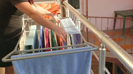 terry : Woman hanging laundry on balcony extended clothes drying rack